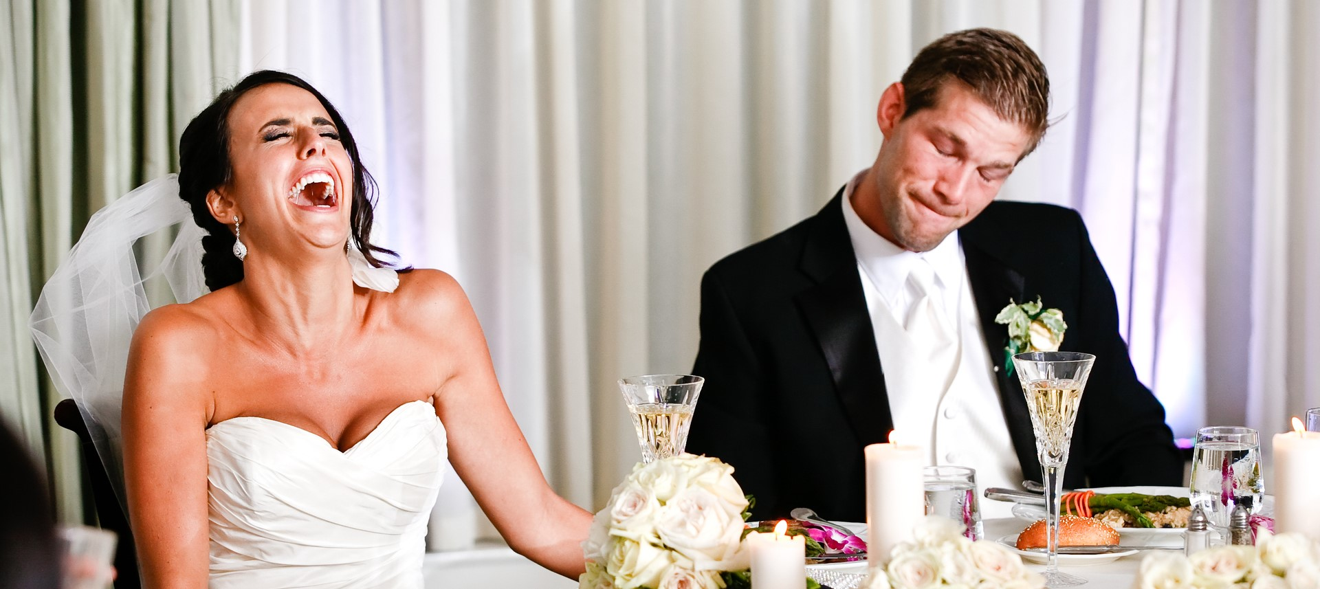 Braut lacht über Anekdote, Bräutigam ist verunsichert, Bräutigam schämt sich, glückliches Brautpaar bei Hochzeitsrede
